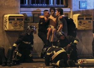 French fire brigade members aid an injured individual near the Bataclan concert hall following fatal shootings in Paris, France, November 13, 2015. At least 30 people were killed in attacks in Paris and a hostage situation was under way at a concert hall in the French capital, French media reported on Friday. REUTERS/Christian Hartmann