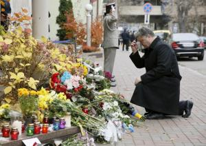 Ukraine's President Petro Poroshenko kneels near the French embassy as he commemorates victims of attacks in Paris, in Kiev, Ukraine, November 14, 2015. REUTERS/Valentyn Ogirenko